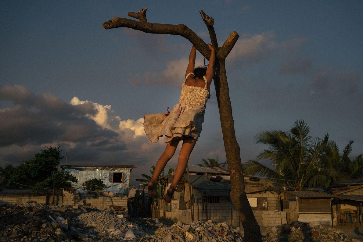 """""""Cette jeune philippine, affectueusement appelée Puti par ses proches, grimpe sur une branche d'arbre à Tondo, ..."""