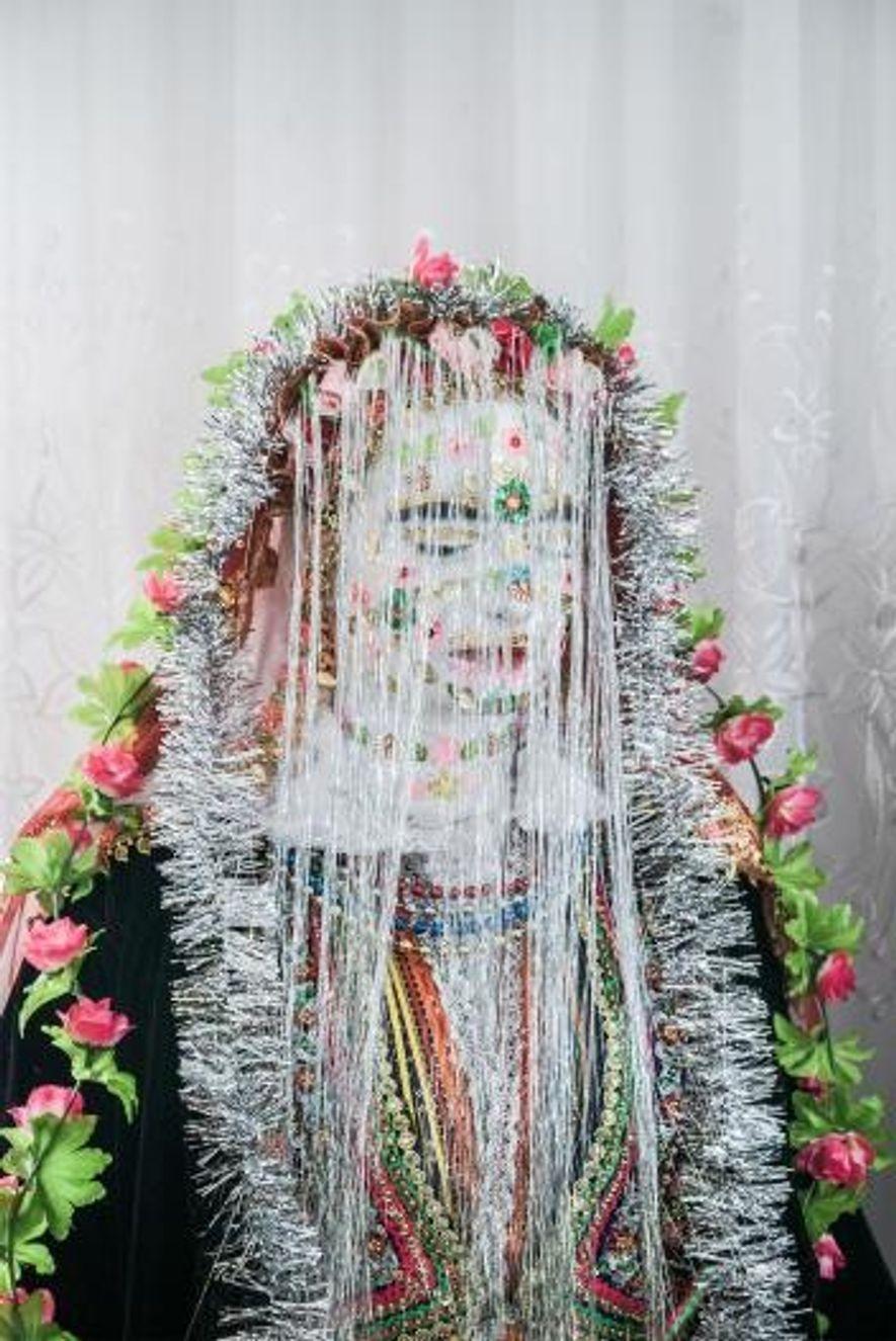 Salve Kiselova sort avec son maquillage terminé et ses yeux fermés, le visage recouvert de guirlandes de Noël.