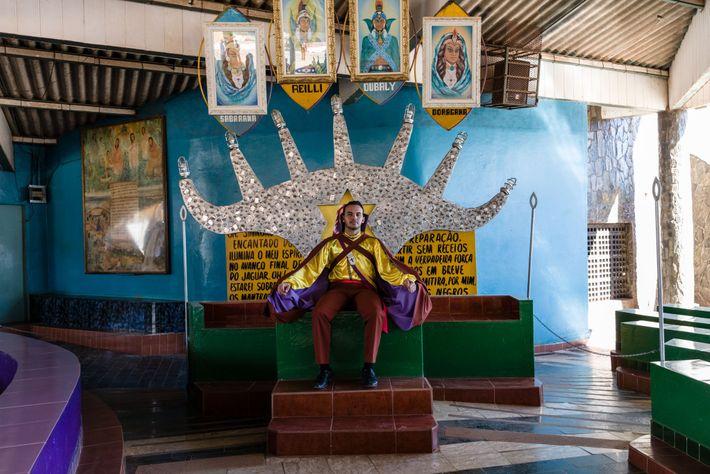 Un adepte de la Vallée de l'aurore vêtu d'un costume de prince maya siège sur un ...