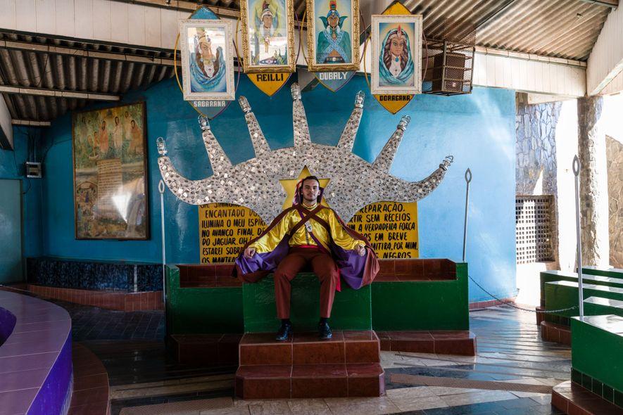 Un adepte de la Vallée de l'aurore vêtu d'un costume de prince maya siège sur un …