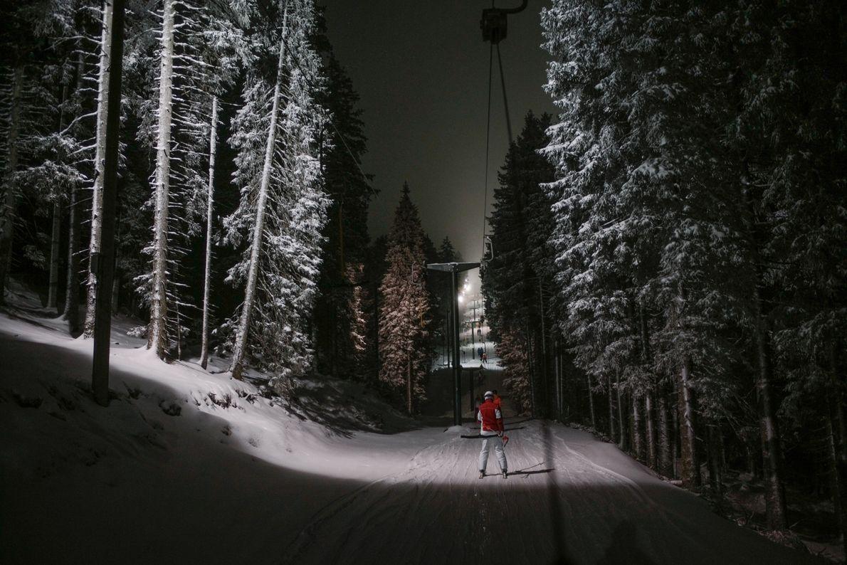 Un skieur remonte en tire-fesse jusqu'au sommet des pistes de ski de Rogla, glissant entre des ...