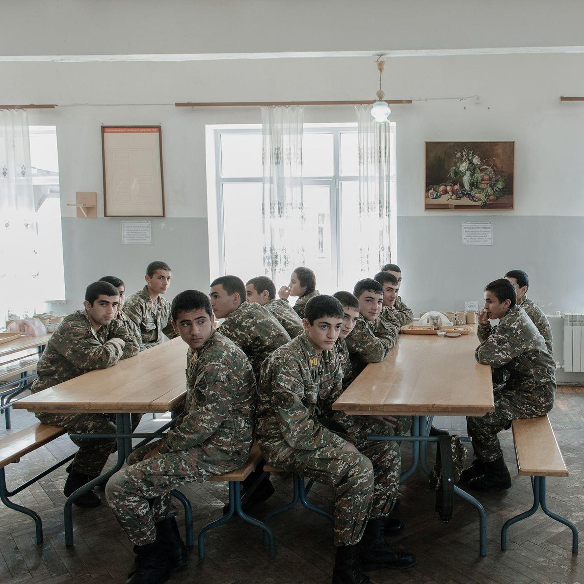 Les jeunes soldats attendent leurs repas dans le réfectoire de l'académie militaire.