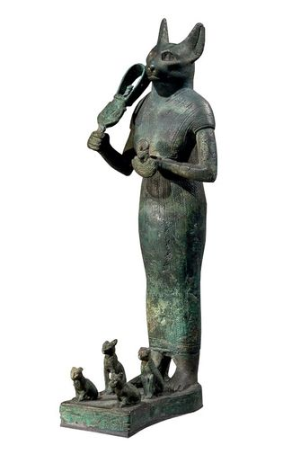 Bastet est représentée ici avec quatre chatons à ses pieds, symbole de fertilité. Elle tient dans sa main ...