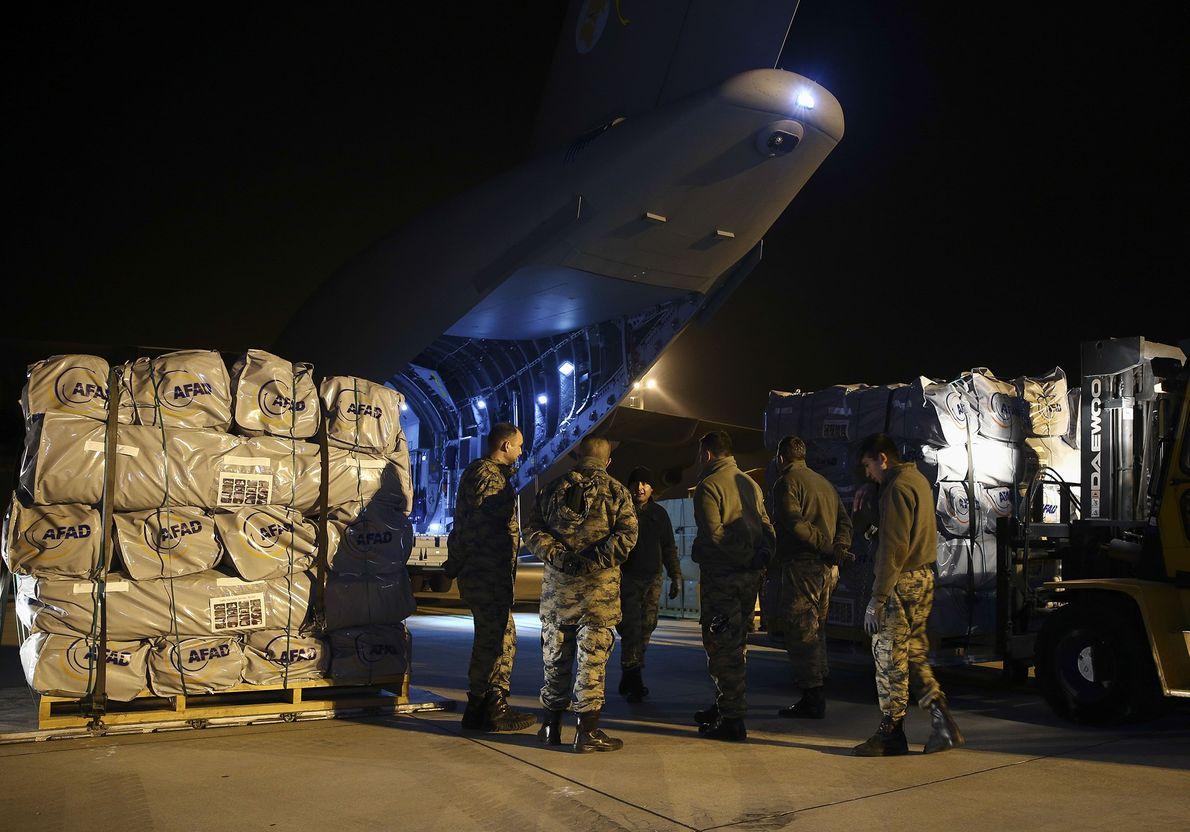 Une équipe de sauveteurs et des soldats attendent l'avion militaire des forces armées turques chargé de ...