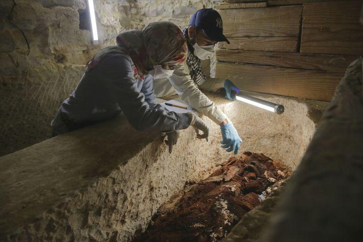Les archéologues Maysa Rabeeh (à gauche) et Mohammed Refaat (à droite) regardent de près le cercueil ...