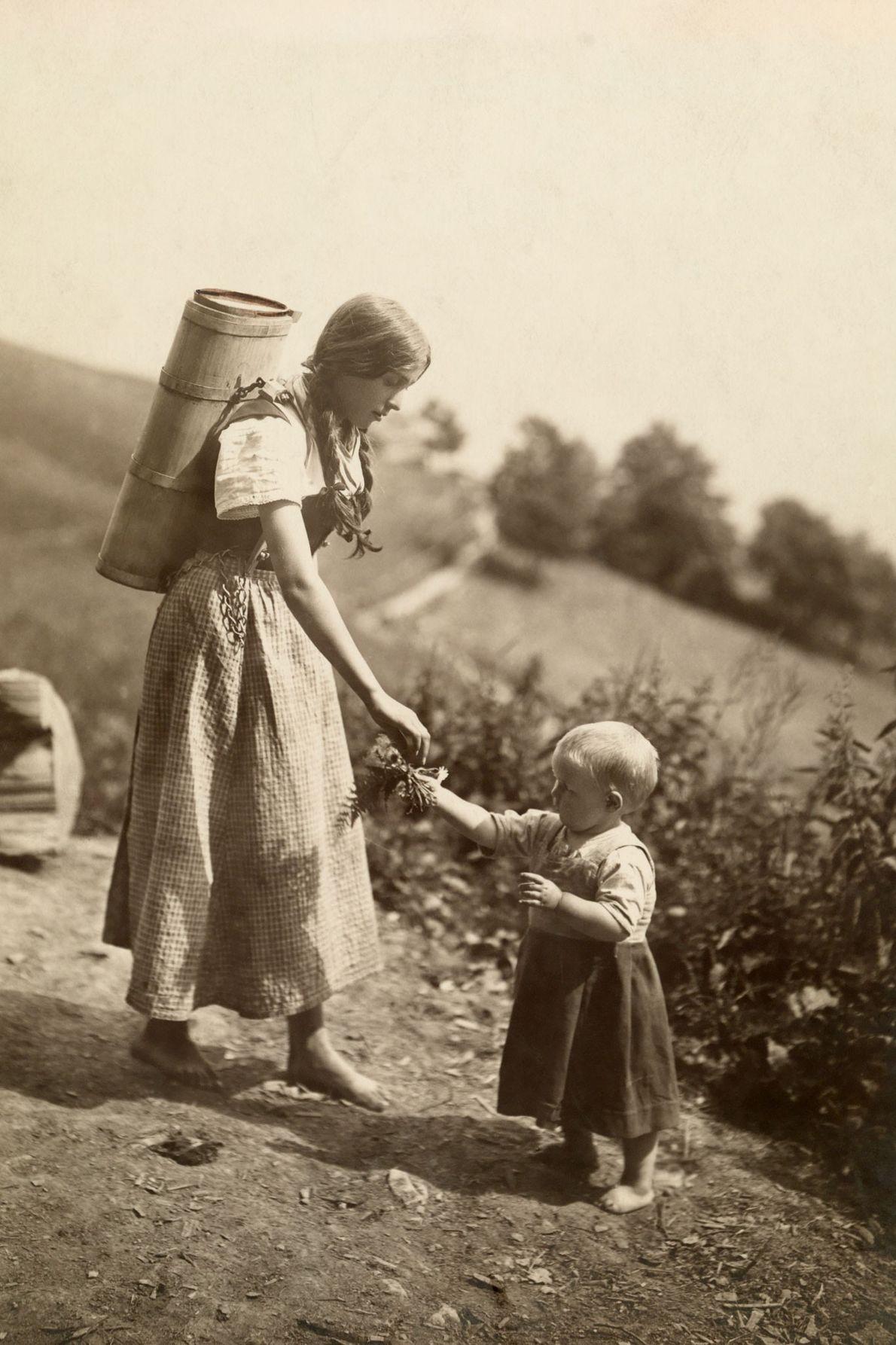 Une mère suisse saisit la main de sa fille, qui lui tend des fleurs.