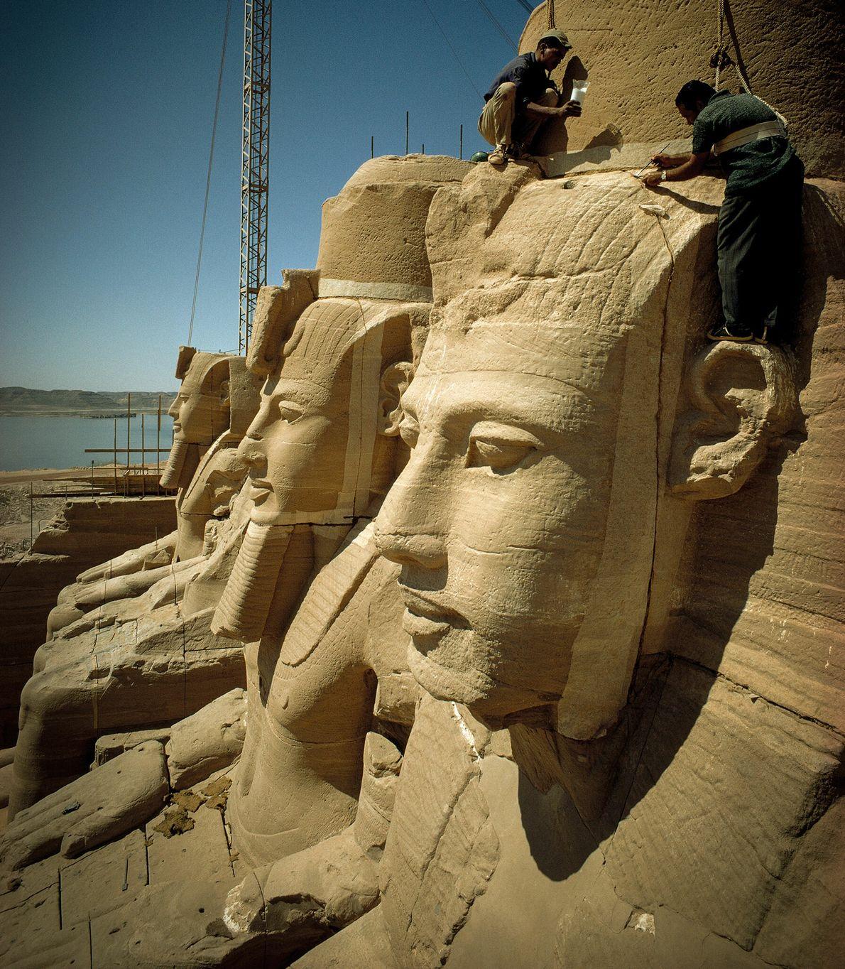 Une fois les blocs de pierre en place, les ouvriers retirent les protections qui couvraient les ...