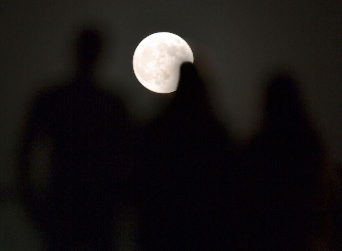 Les gens regardent l'éclipse lunaire depuis le Centre de la civilisation et de la créativité des ...