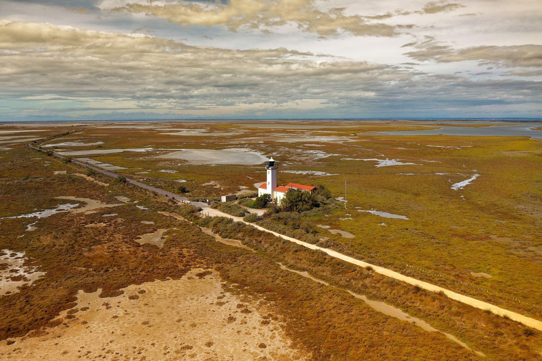 Le Phare de la Gacholle et la digue reliant les Saintes-Maries-de-la-Mer au Salin de Giraud, en ...