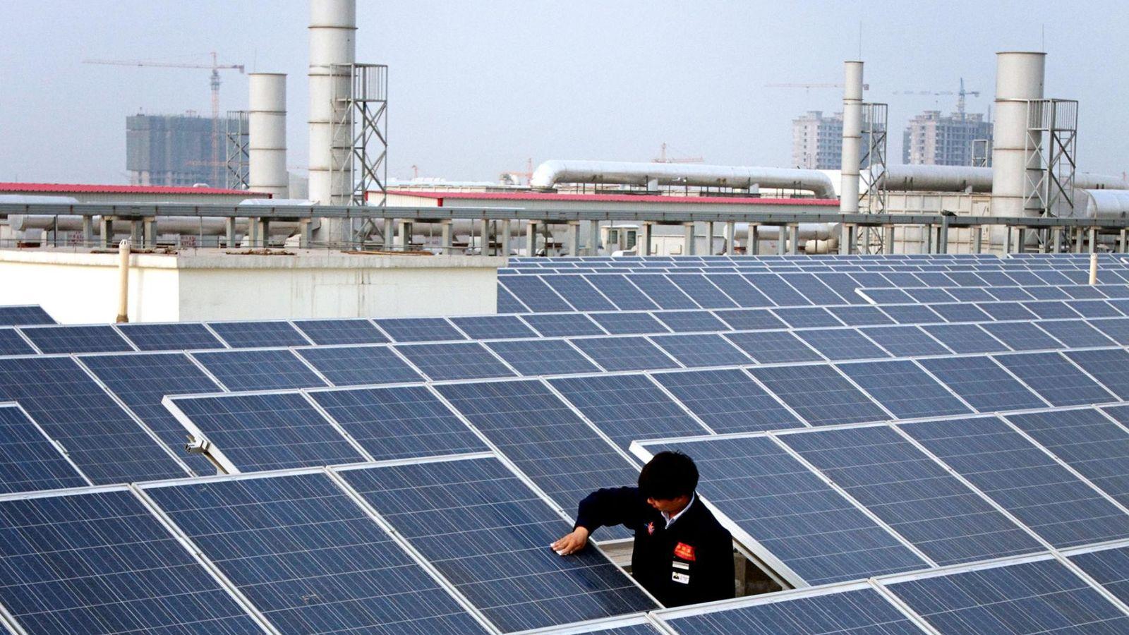 Un ouvrier nettoie un panneau solaire sur le toit d'une usine dans la ville de Baoding. ...