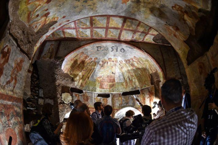 Des visiteurs admirent une fresque restaurée dans les catacombes de Domitille, à Rome.