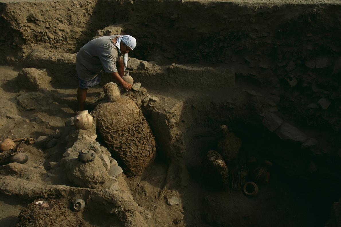 Un archéologue excave un artefact près de restes de momies incas. Des milliers de ces restes ...