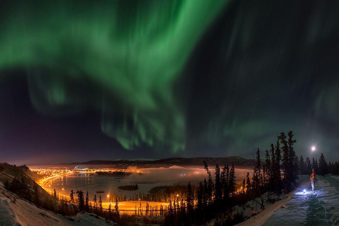 Un homme observe les aurores boréales qui colorent le ciel de Yukon, au Canada.