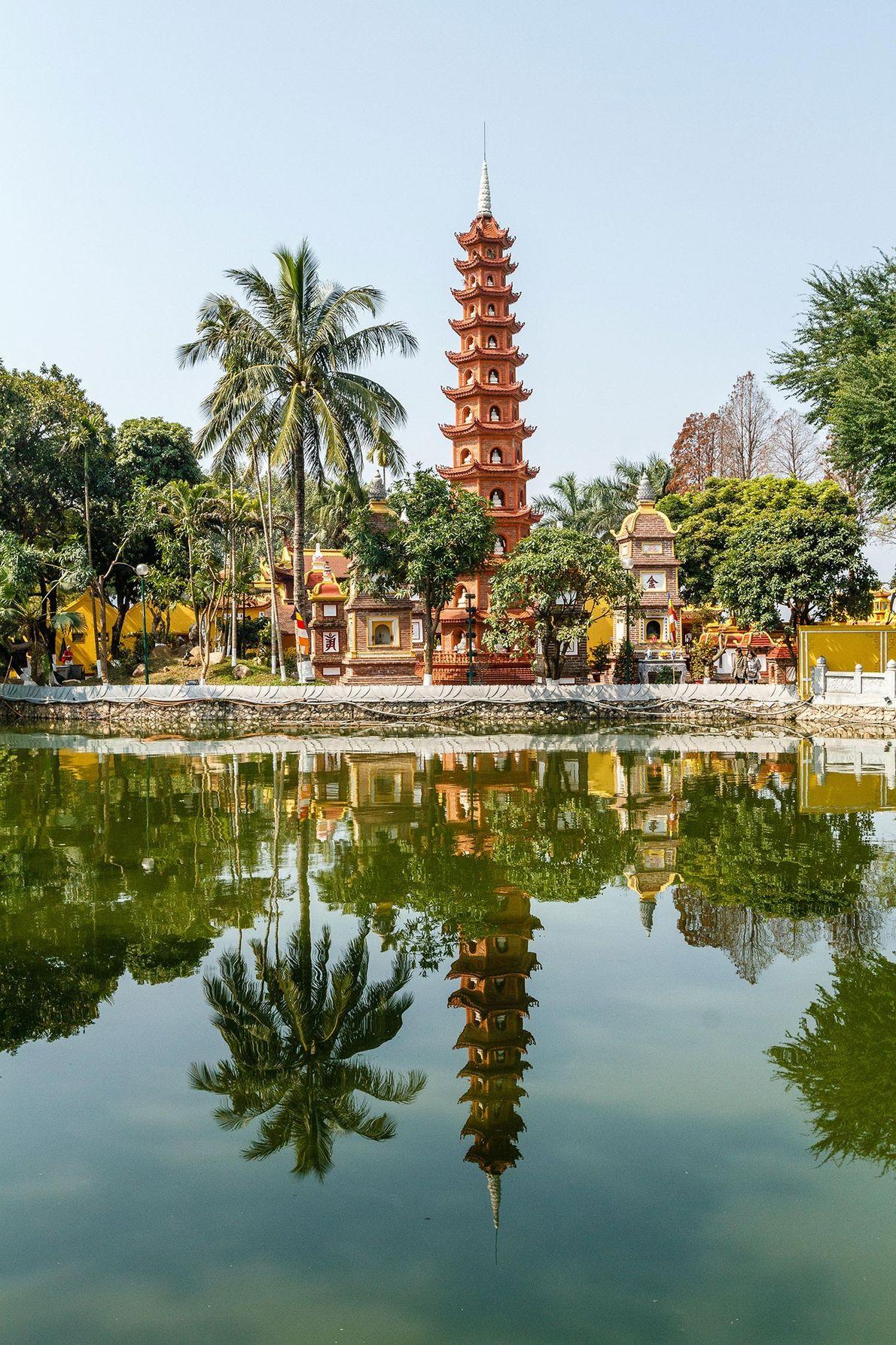 Datant du 6e siècle, la pagode Trấn Quốc flotte sur une petite île entourée par les eaux ...