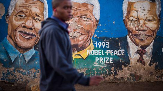 Un homme passe devant un mur arborant plusieurs images de Nelson Mandela dans la rue Khumalo ...