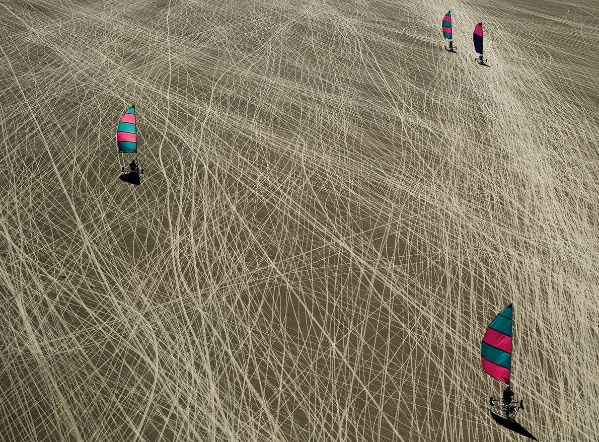 Des chars à voile dessinent dans le sable