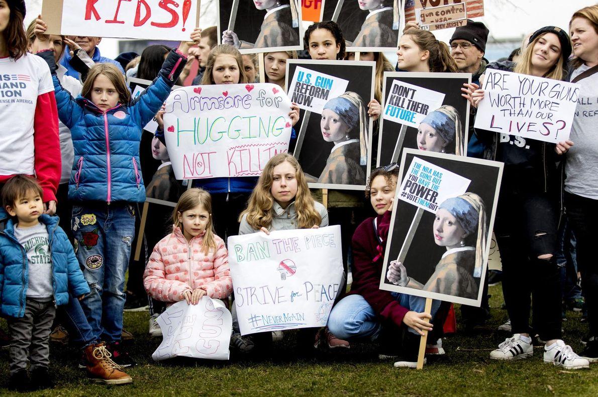 Dans le centre d'Amsterdam, sur la place des musées, de jeunes manifestants et leur pancarte protestent ...
