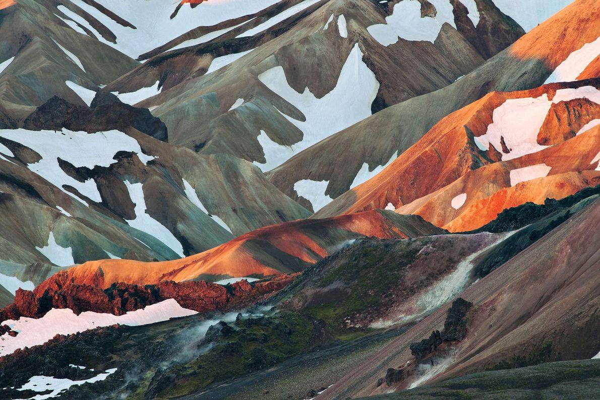 Les premiers rayons de soleil d'une matinée de juin illuminent une crête de rhyolite volcanique de ...