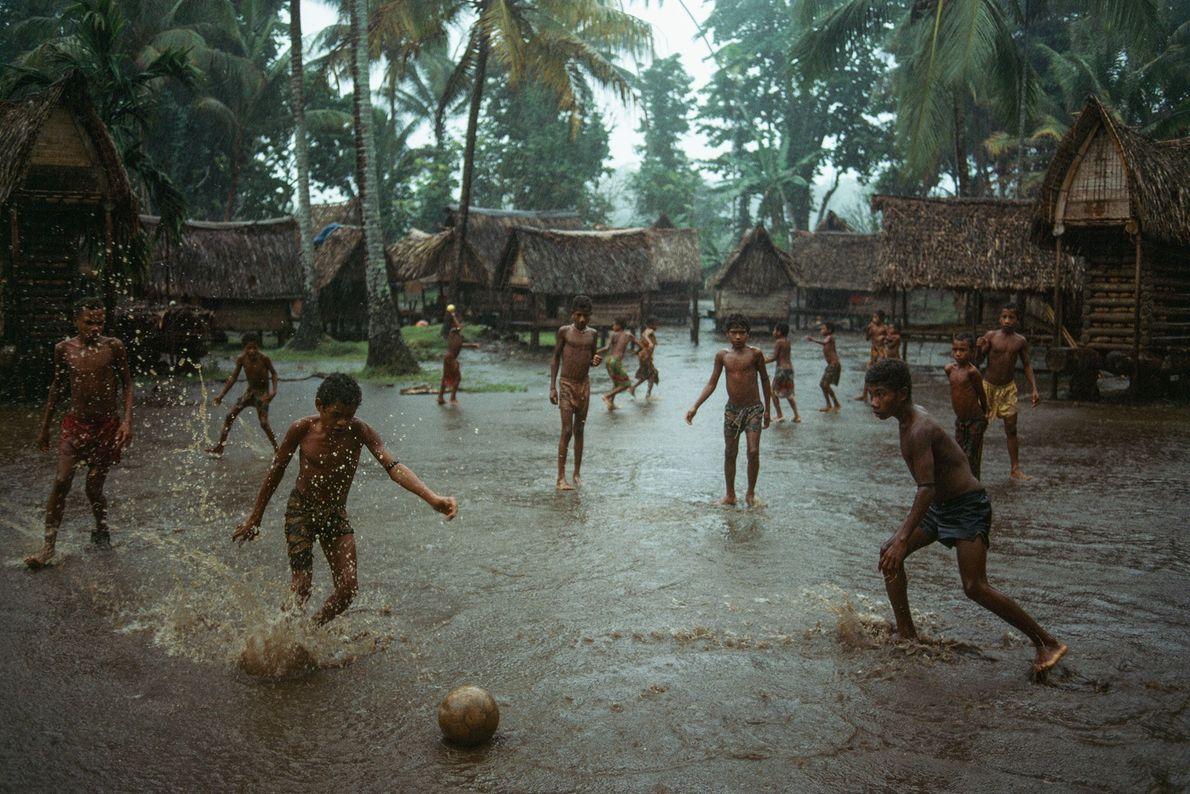Des garçons jouent au football dans un village inondé de Kiriwina, la plus grande des îles ...