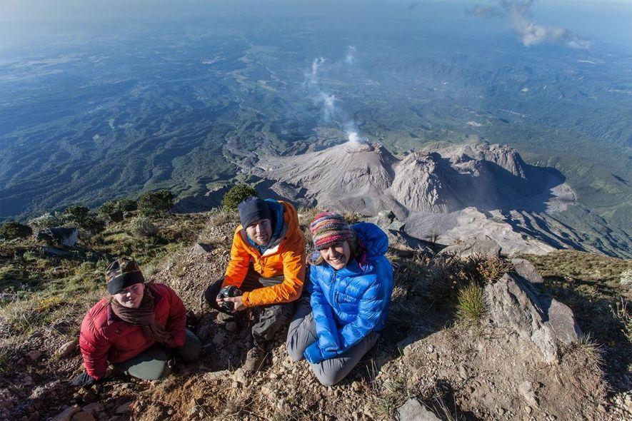 Ross Donihue, Stephanie Grocke et Gabby Salazar prennent la pause au sommet du volcan Santa María. Les dômes de lave du Santiaguito sont visibles en arrière-plan.