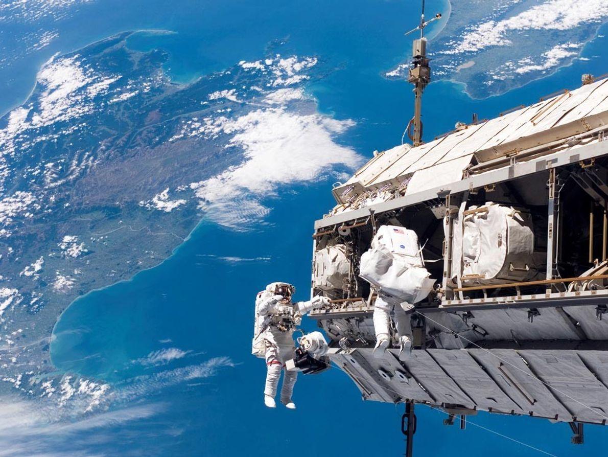 En 2006, lors d'une sortie dans l'espace, les spécialistes de mission, Robert Curbeam, à gauche, et ...