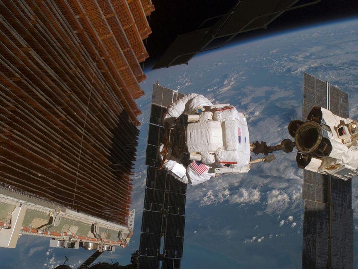 L'astronaute Robert Curbeam travaille sur l'aile solaire gauche de la poutre P6 de la Station spatiale ...