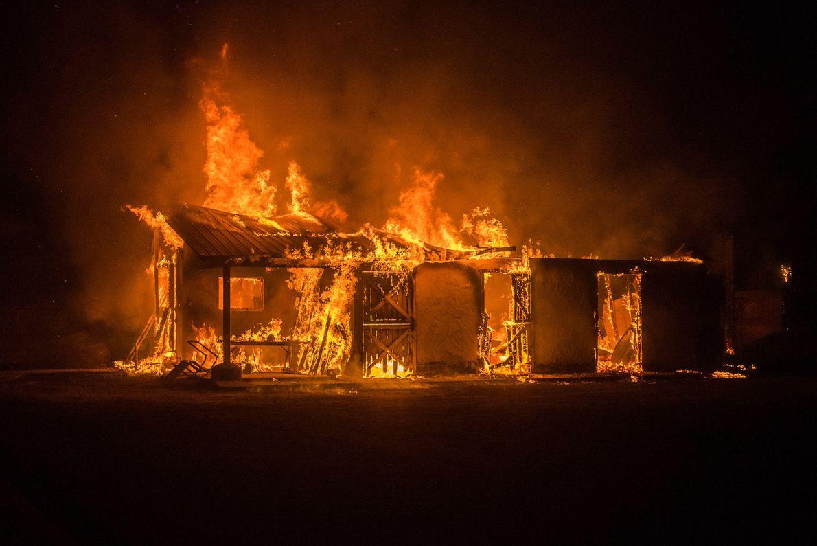 Un bâtiment est en feu suite à l'incendie River en Californie, malgré les efforts des avions ...