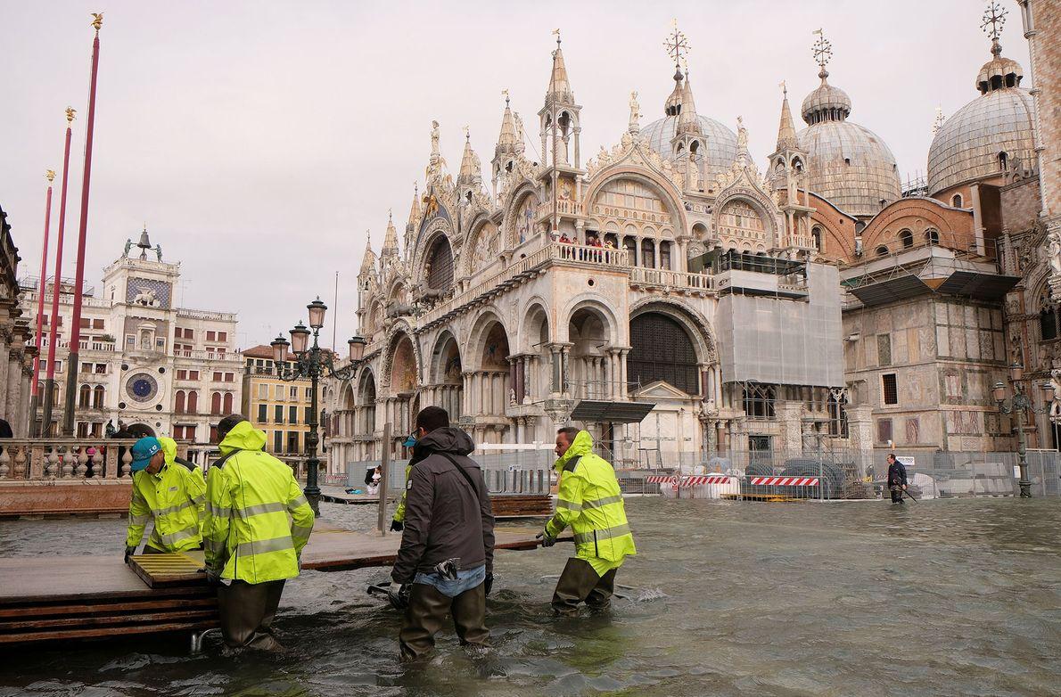 Des employés municipaux préparent une passerelle temporaire sur la place Saint-Marc inondée.