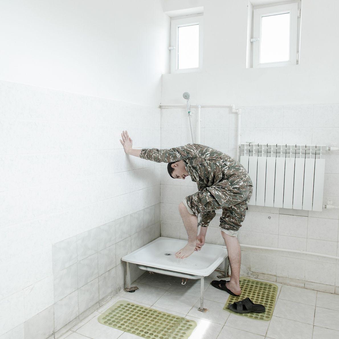Après les cours et l'entraînement, un jeune soldat lave ses pieds dans la salle de bain ...