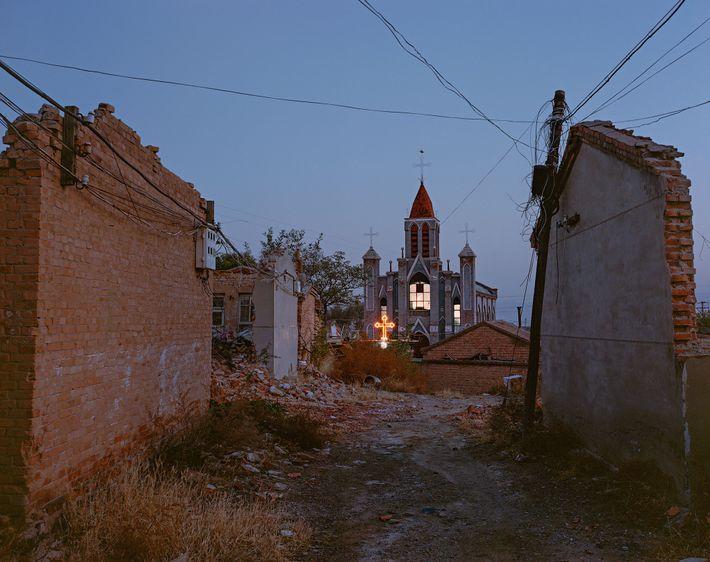 La lumière brille toujours à l'intérieur d'une église catholique d'un village du district de Xiahuayuan où ...