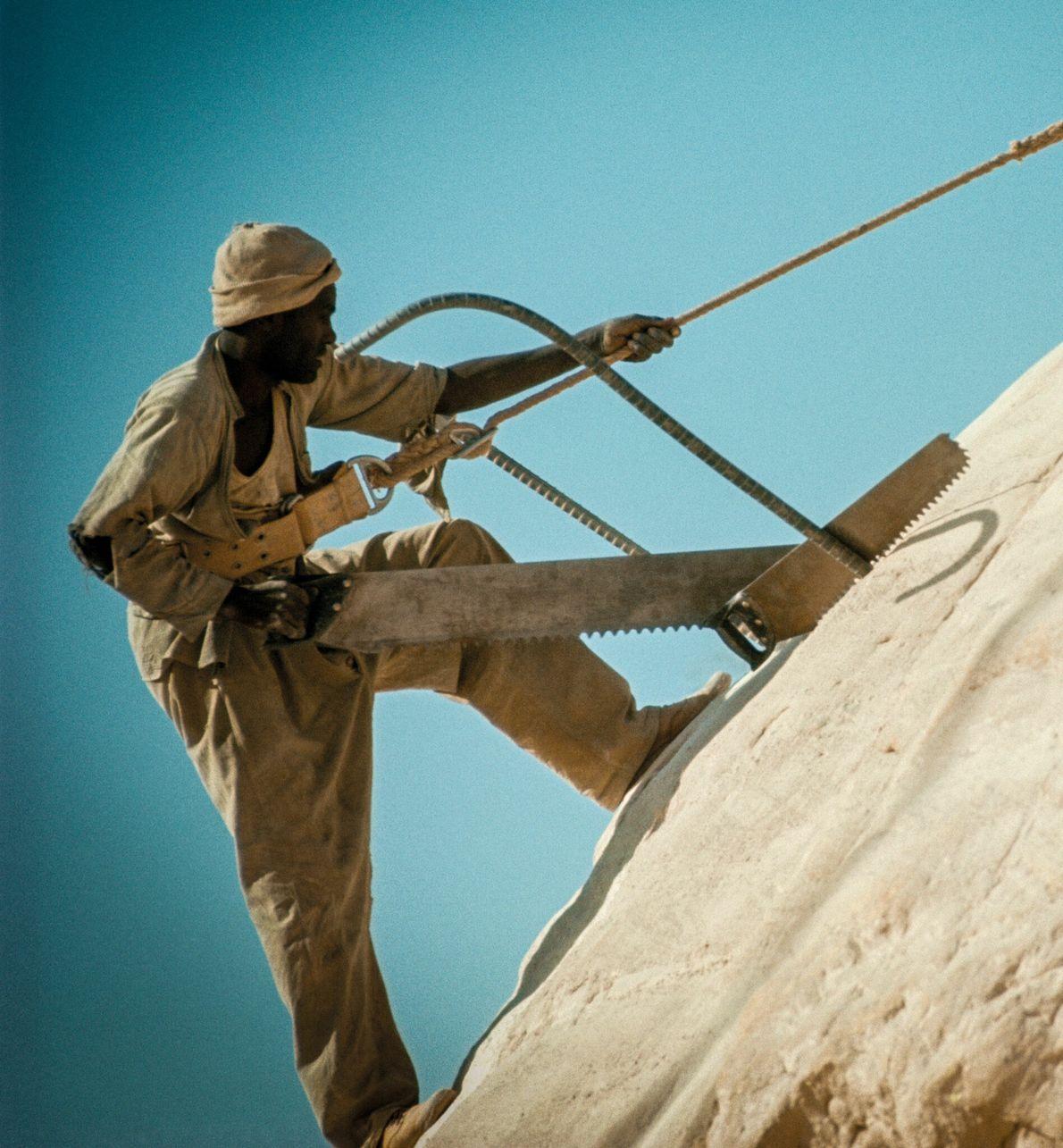 Un tailleur de pierre réalise une incision précise sur l'extérieur d'un temple d'Abou Simbel à l'aide d'une ...
