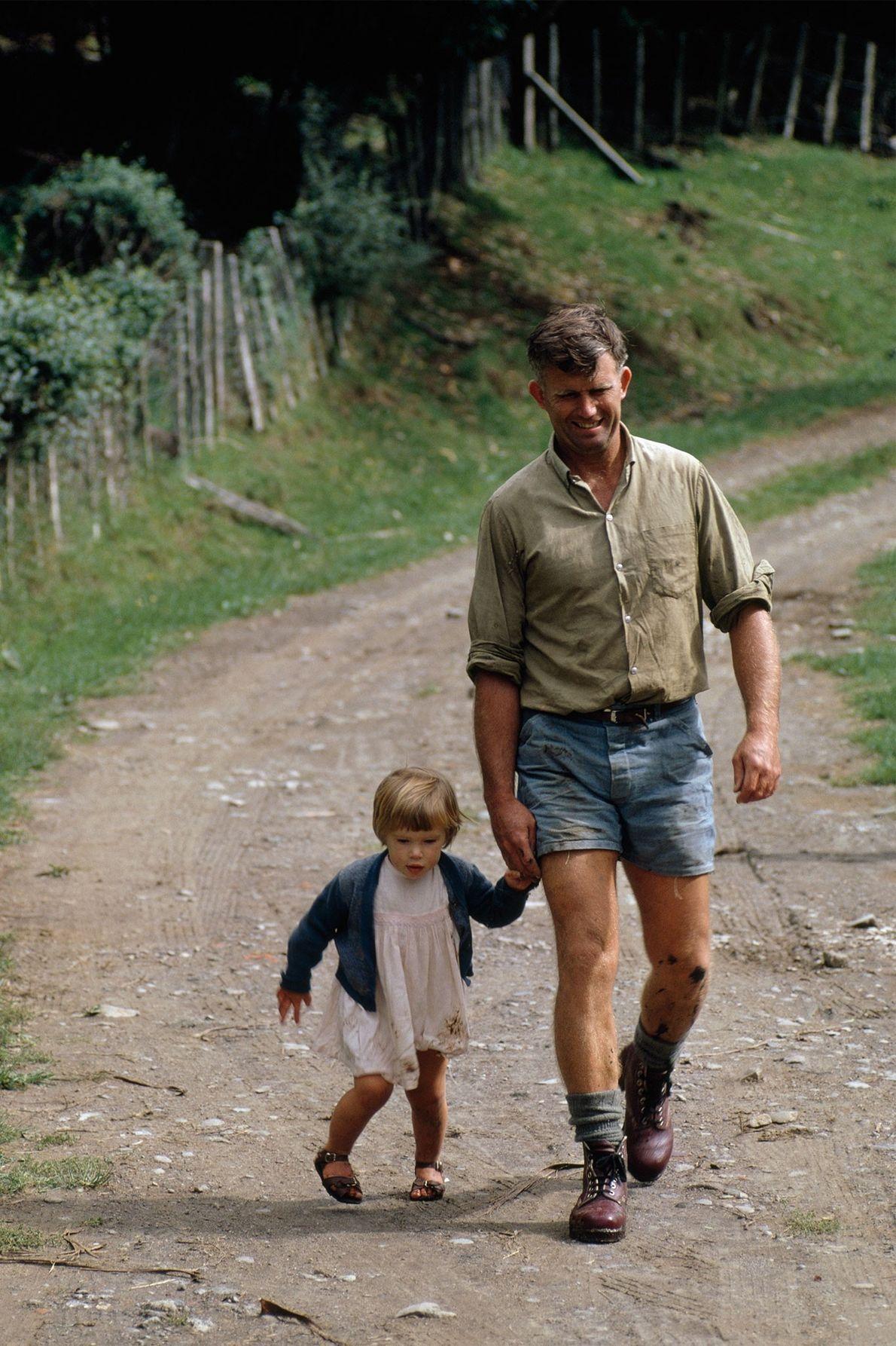 Un agriculteur marche avec sa fille sur un chemin de terre sur l'île du Nord de ...