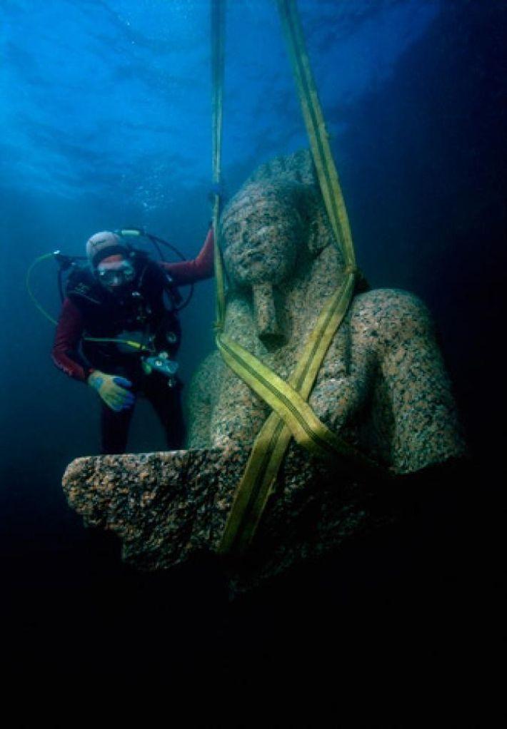 La moitié supérieure d'un colosse en granit est hissée à la surface de la baie d'Aboukir, ...
