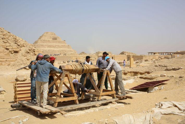 Les travailleurs utilisent un treuil à manivelle pour faire parvenir les outils et autres équipements à ...