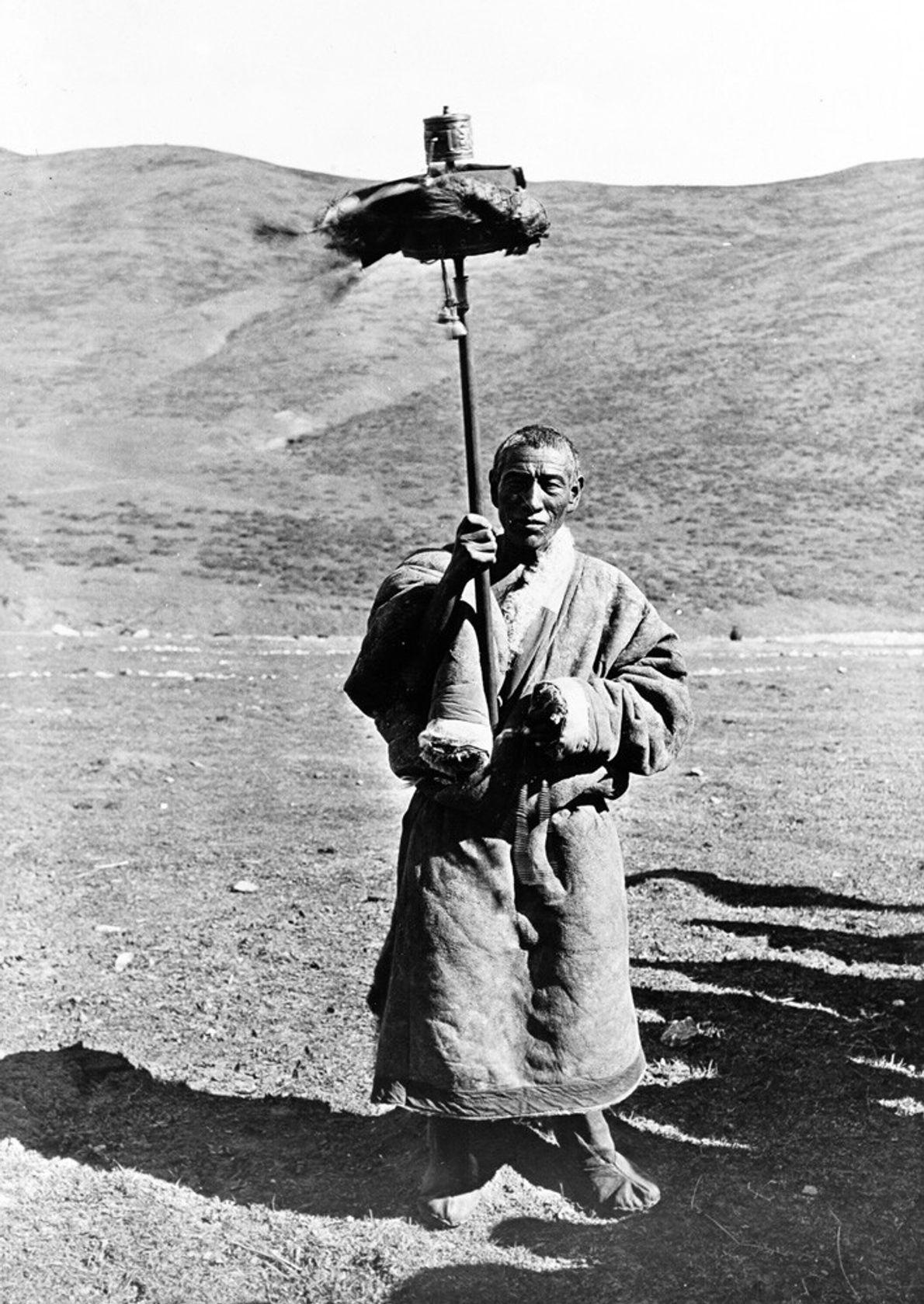 Tibet, 1955 : un nomade tibétain Drokpa fait pivoter un grand moulin à prières le long de ...