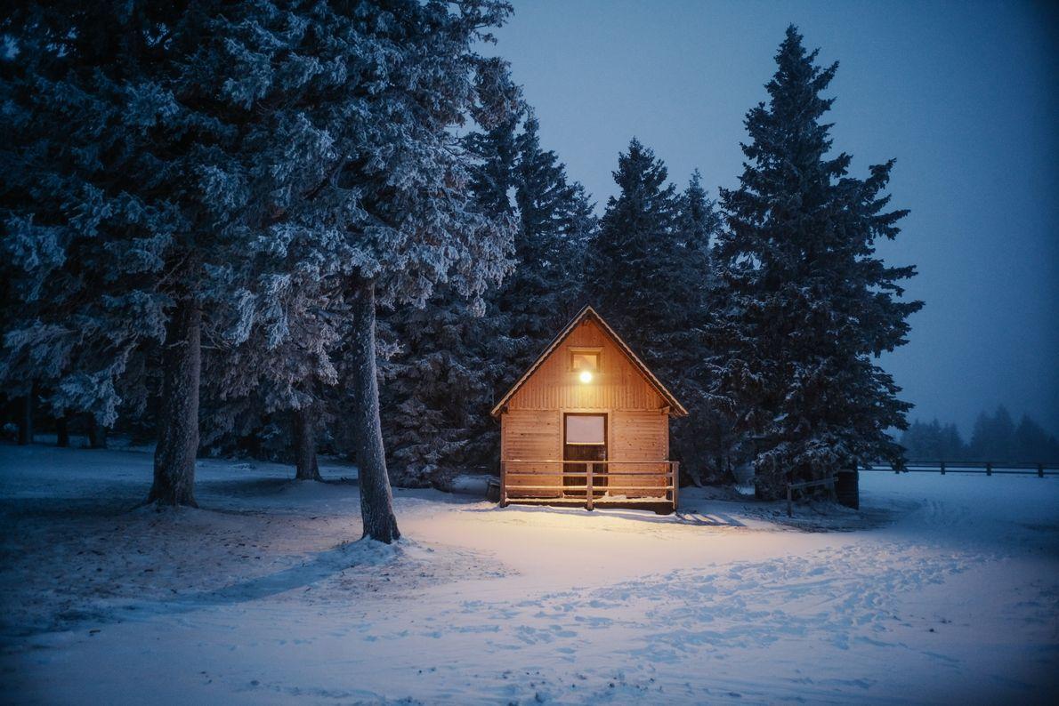 Alors que la nuit approche, une chaude lueur illumine l'une des rustiques huttes de montagne de ...