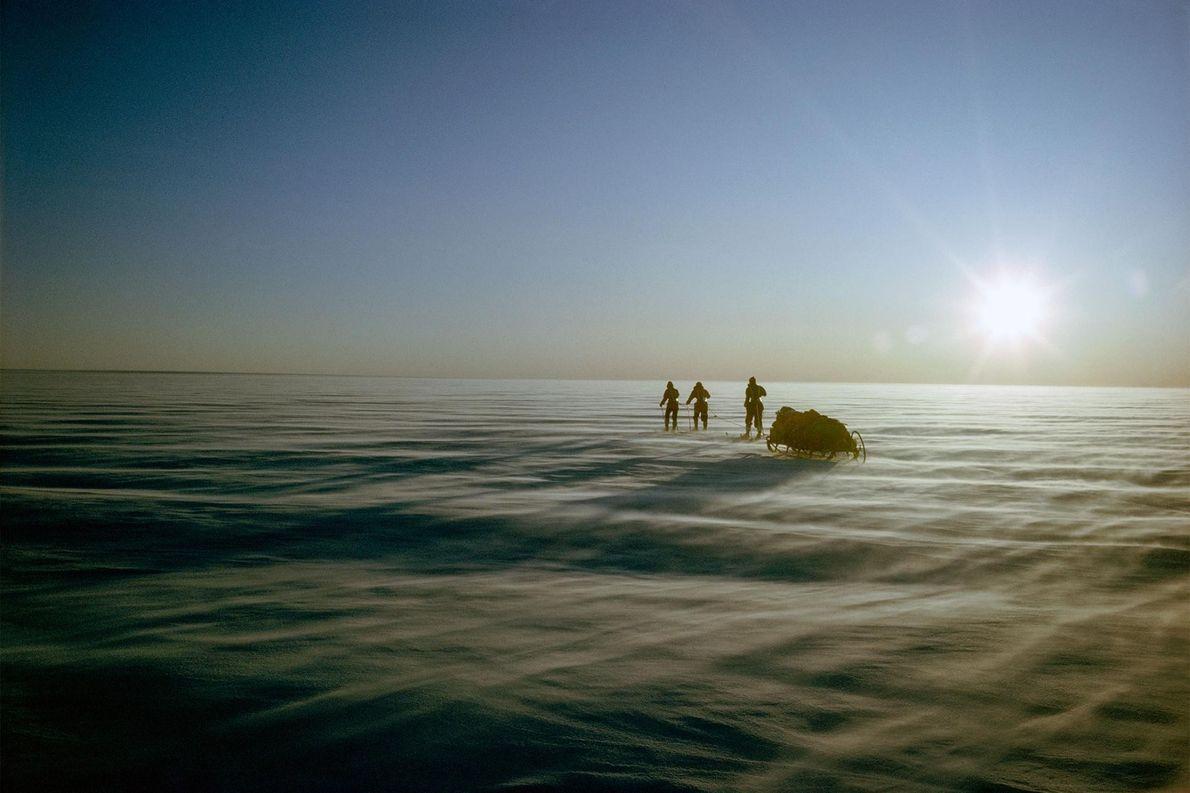 L'équipe tire son traîneau au milieu de la banquise du Groenland. Pour se protéger du soleil ...