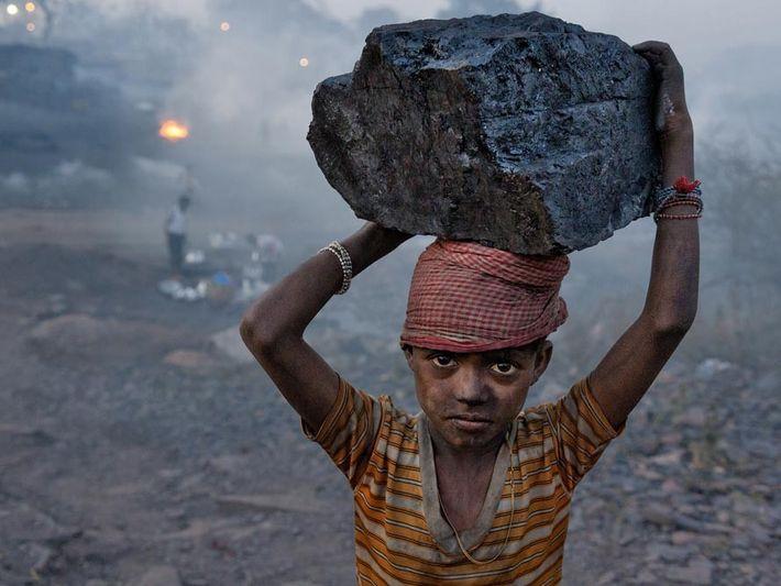 Jharkhand, Inde - Un jeune garçon transporte un énorme morceau de charbon dans le camp minier ...