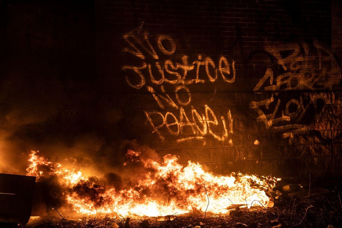 """Des graffitis expriment la colère des manifestant """"Pas de justice, pas de paix""""sur l'un des mursdu ..."""