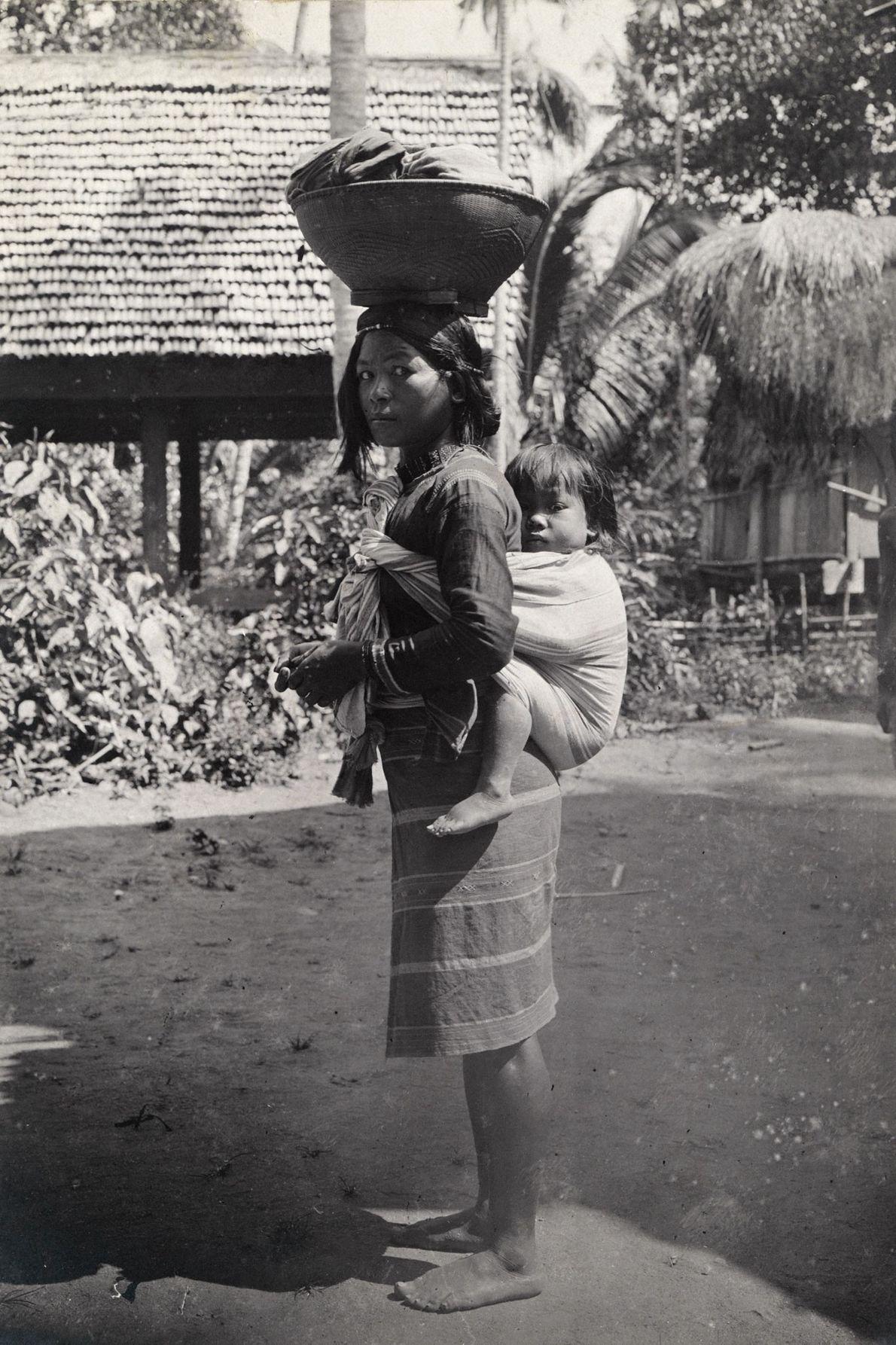Une femme tingian porte un enfant sur son dos et équilibre un panier sur sa tête ...