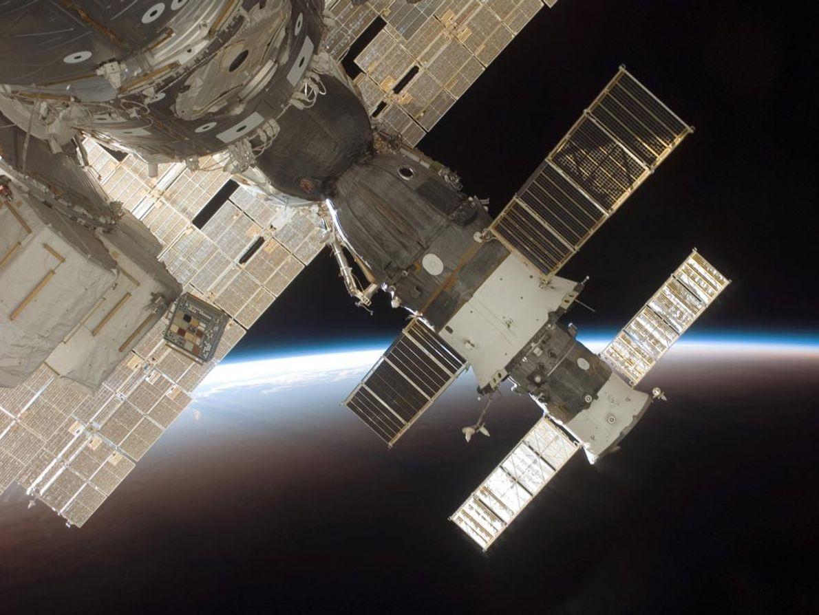Photographie de la fusée Soyouz 13 arrimée et du vaisseau cargo Progress 22, alors qu'en arrière-plan, ...
