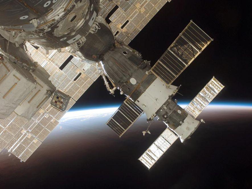 Photographie de la fusée Soyouz 13 arrimée et du vaisseau cargo Progress 22, alors qu'en arrière-plan, …