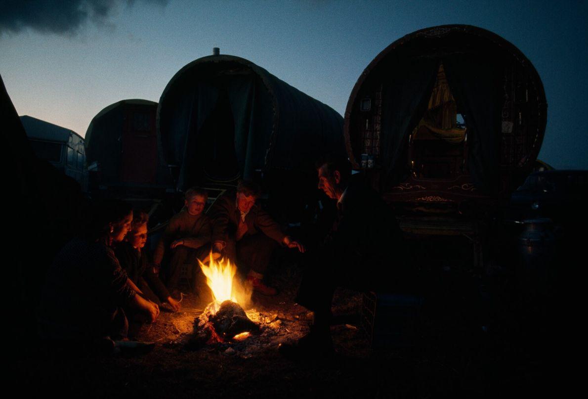 Angleterre, 1972 : assis devant des roulottes traditionnelles, une famille de voyageurs cuisine autour du feu. Les ...