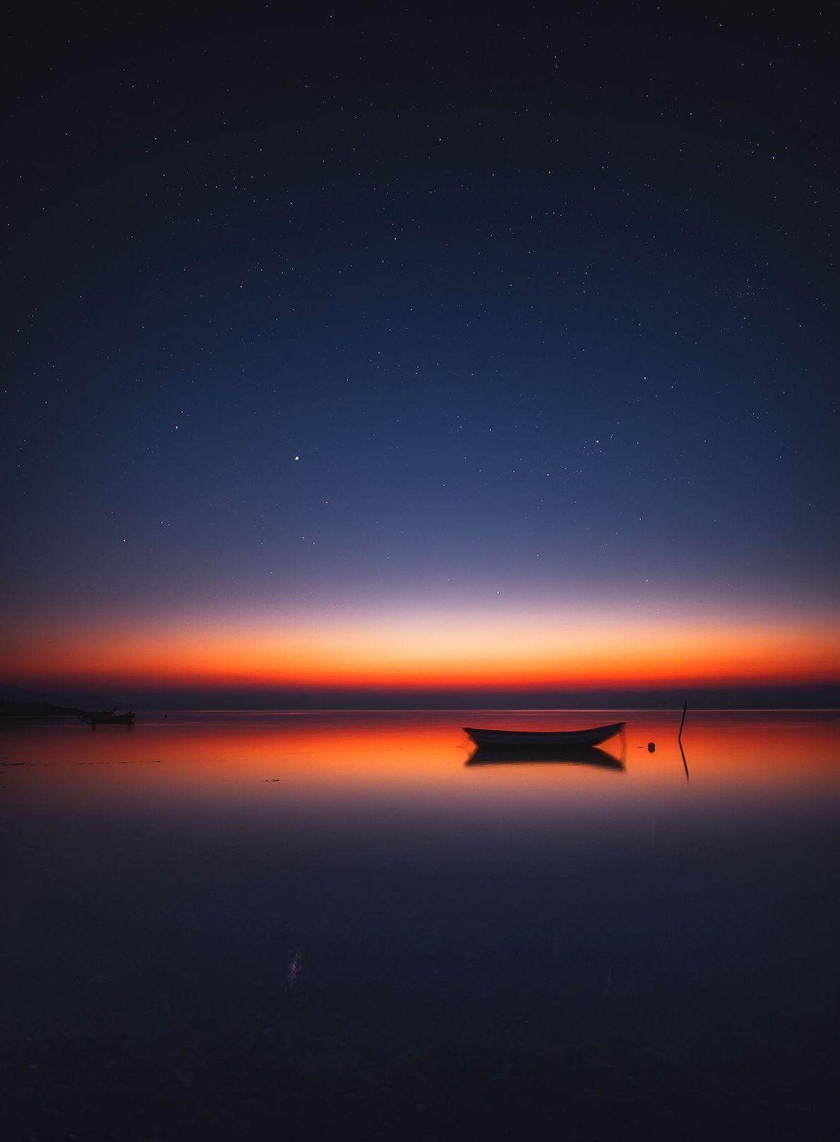 Des lueurs orangées s'emparent de la nuit noire par-dessus le Limfjord à Nykøbing Mors au Danemark.