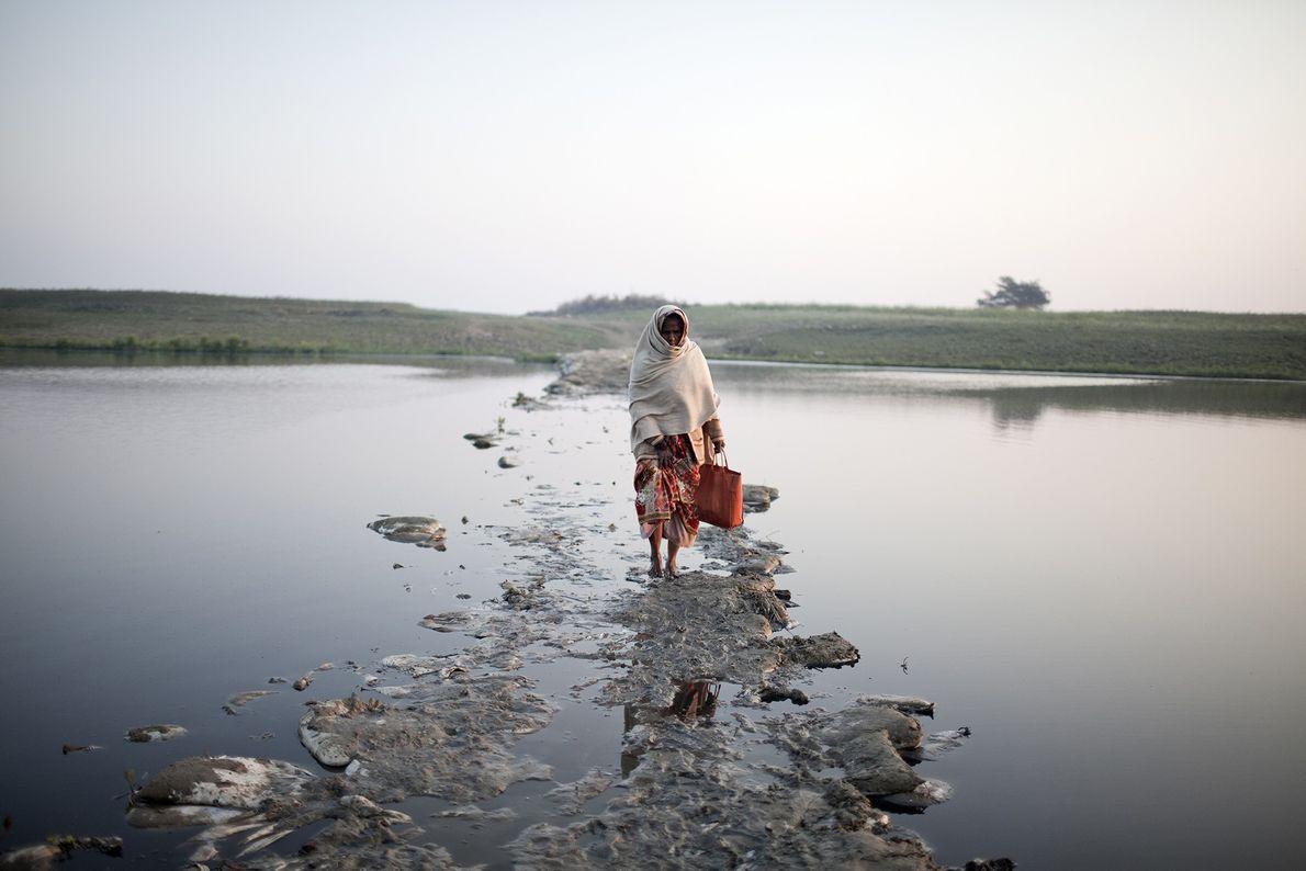 Une femme traverse un petit canal du Gange sur un pont submergé de déchets.