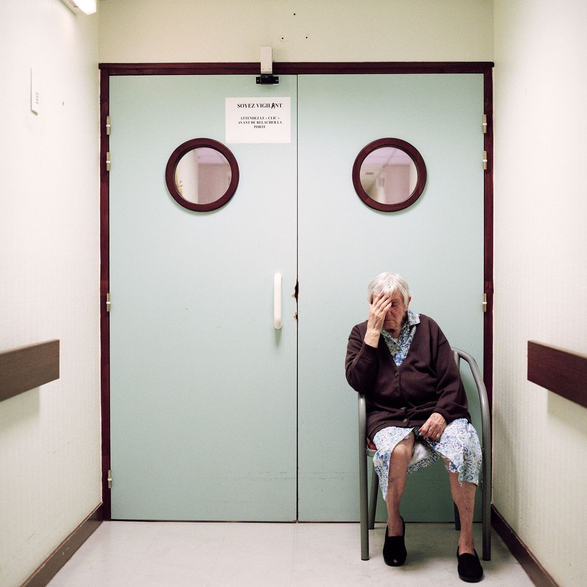 Une résidente est assise devant la porte verrouillée menant à la sortie du département.
