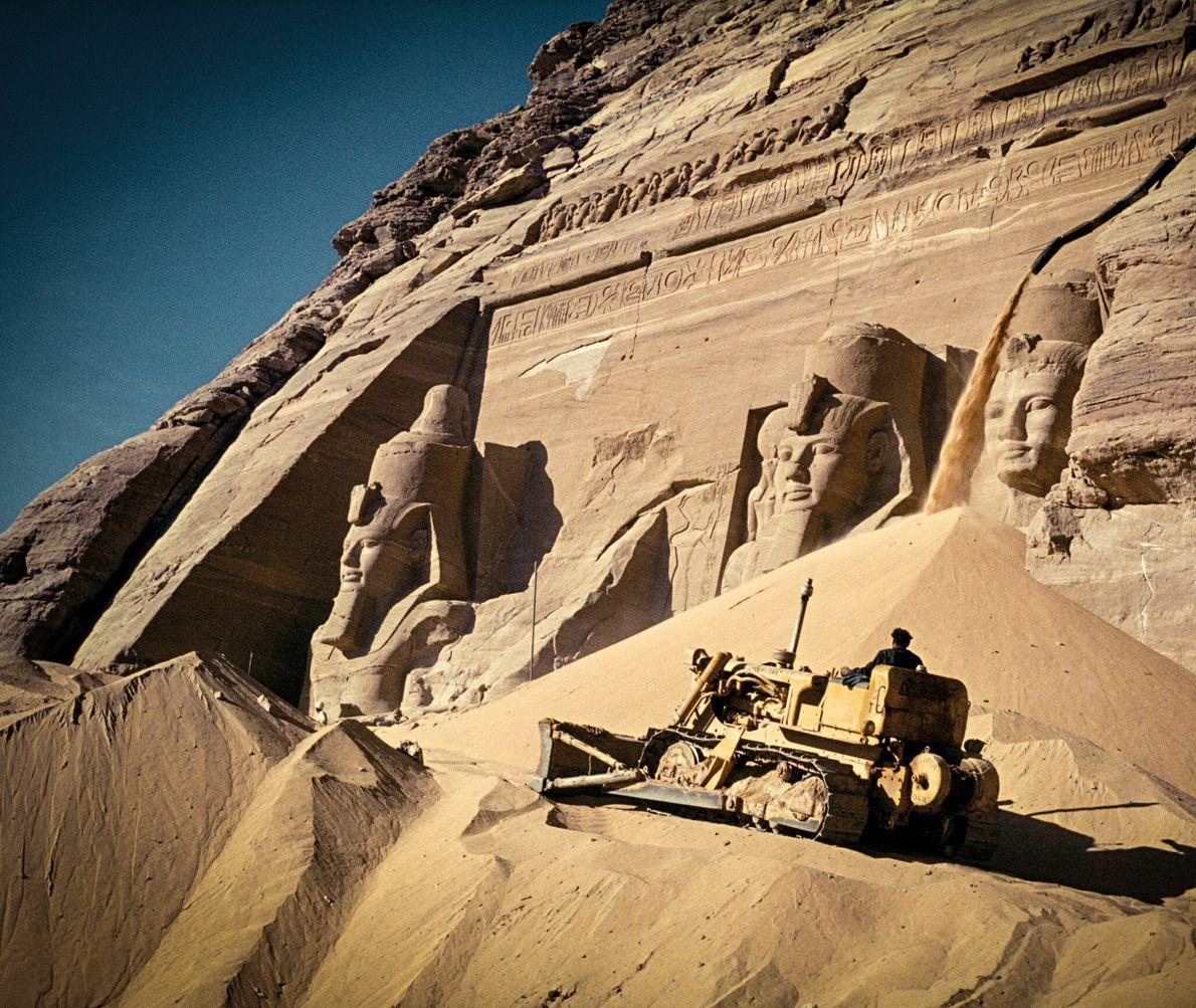 Un bulldozer gravit une rampe de sable devant le Grand temple de Ramsès II. La rampe permettait ...