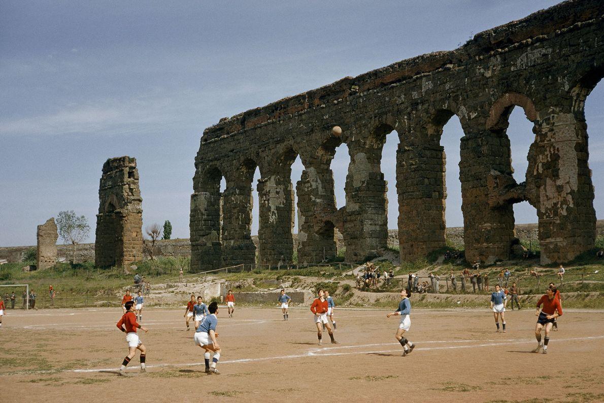 Des garçons jouent au football à côté des ruines d'un aqueduc en 1957, à Rome, en ...