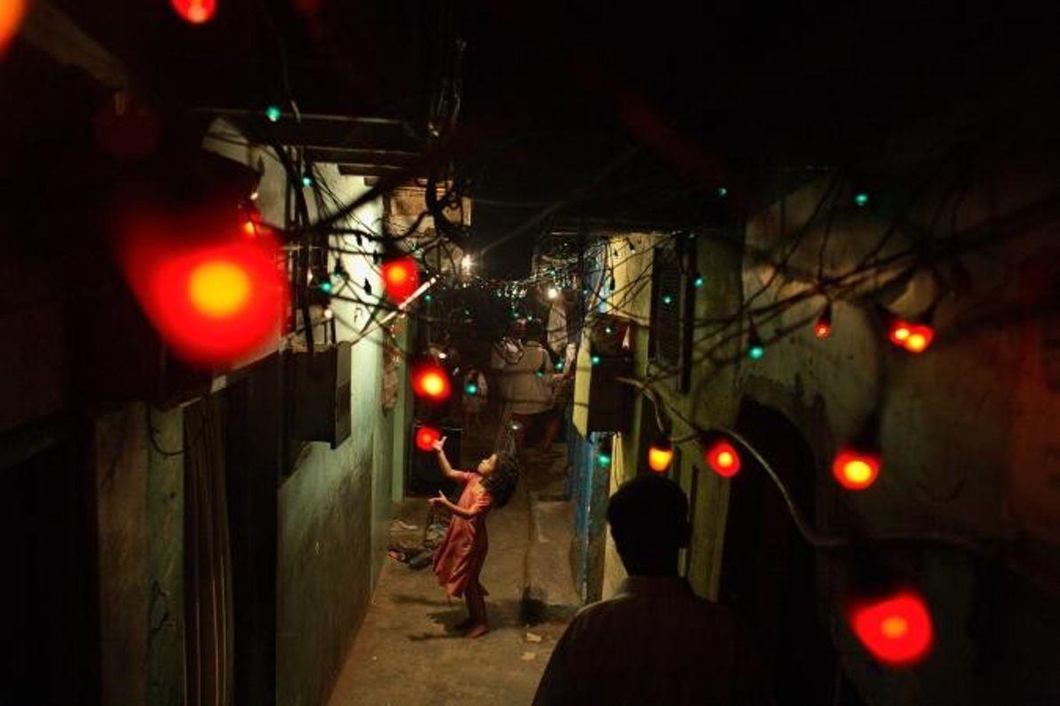 À Dharavi, en Inde, un enfant joue avec les lampions rouges qui décorent une rue, signe ...