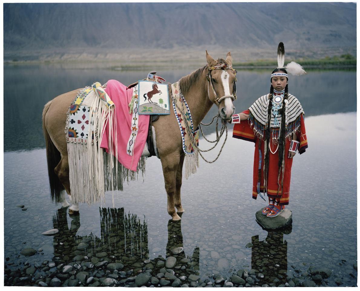Dans l'État de Washington, debout sur une pierre entourée d'eau, une fille de la tribu Wanapum ...